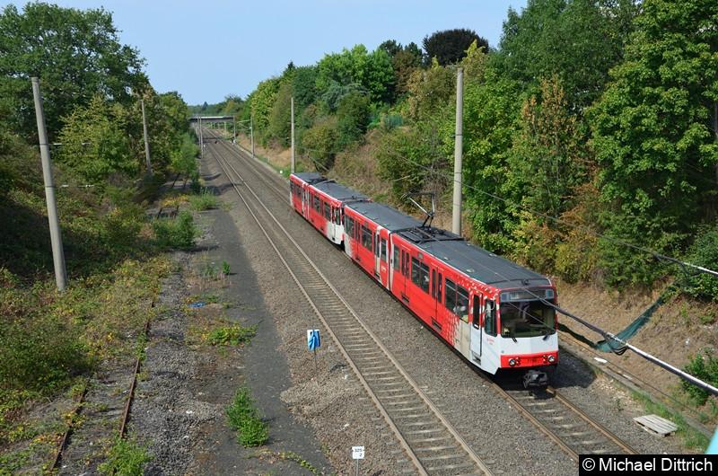 7760 am Ende des Zugs noch mit Rollbändern auf dem Weg nach Köln beim Verlassen der Haltestelle Buschdorf.